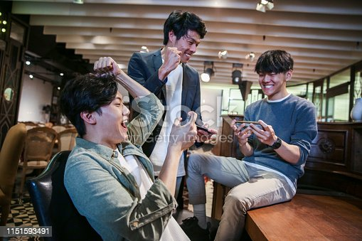 Young friends playing mobile game in cafe