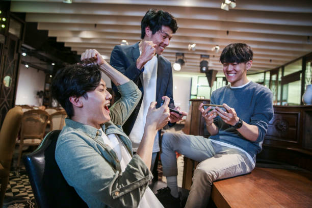 young friends playing mobile game in cafe - mobile game stock photos and pictures