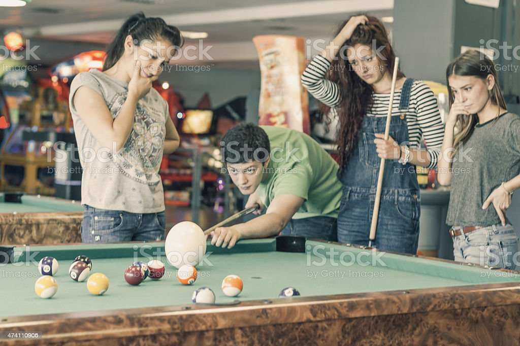 Young friends playing pool or billiard with ostrich egg stock photo