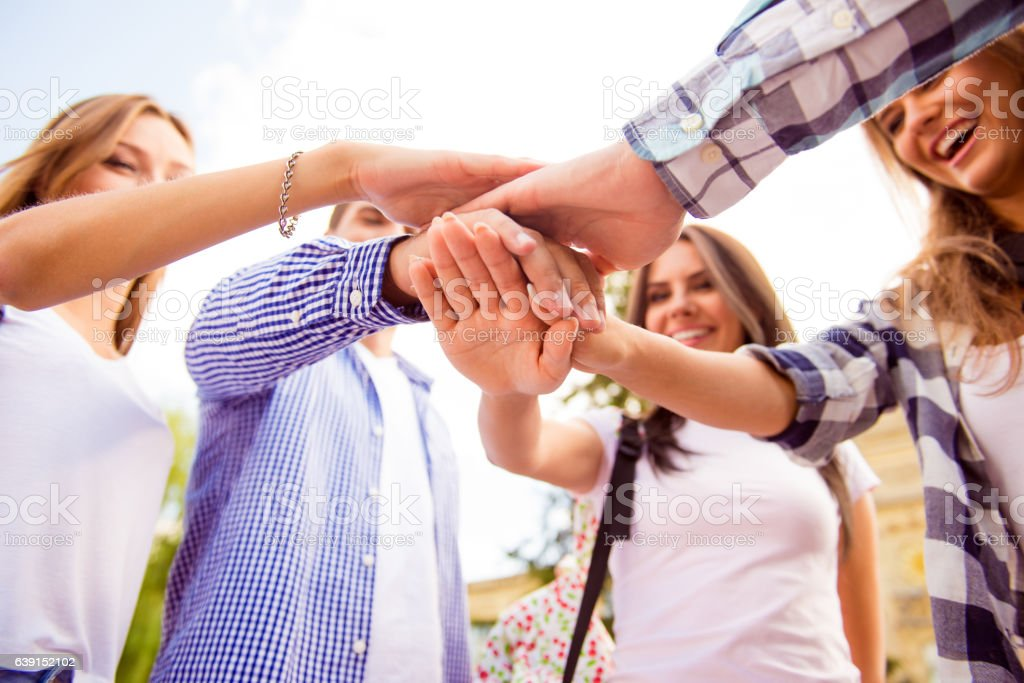 young friends putting their hands on top of each other stock photo