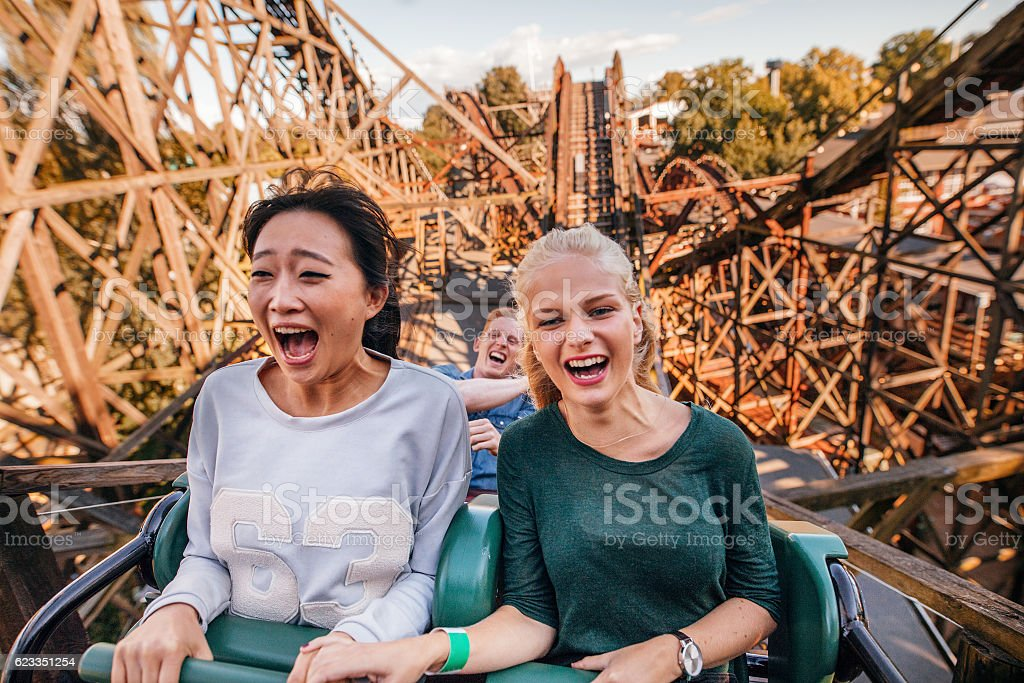 Young friends riding roller coaster ride stock photo