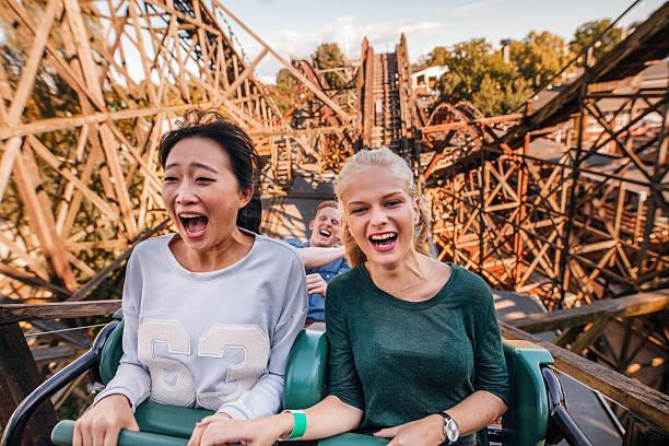 young friends riding roller coaster ride - fahrgeschäft stock-fotos und bilder