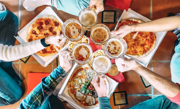 Young friends roomates eating take away pizza at home after college - Friendship concept with people students enjoying time together and having fun at shared apartment - Focus on beer pint glasses stock photo
