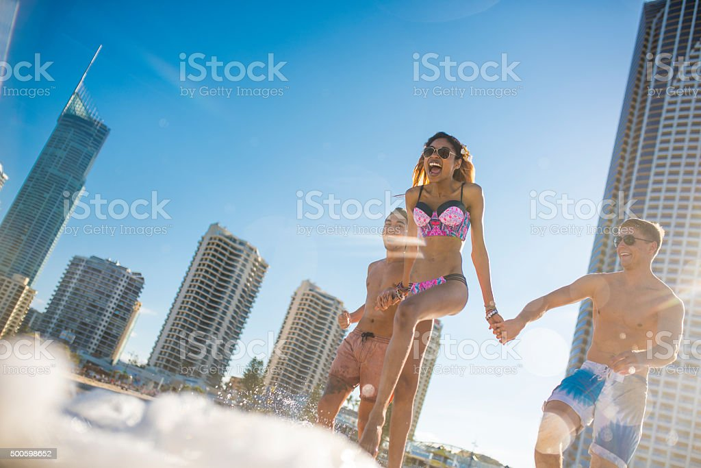 Young friends running into the sea stock photo