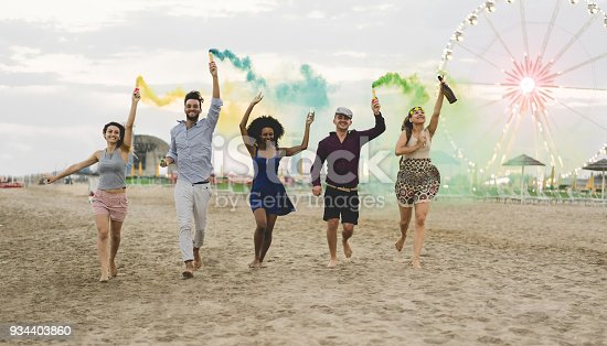 istock Young friends running with smoke bombs and champagne bottle at beach festival - Happy people having fun in summer vacation - Friendship, youth and party concept - Main focus on left guys 934403860