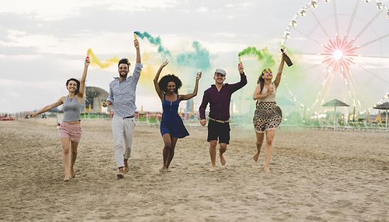 Young friends running with smoke bombs and champagne bottle at beach festival - Happy people having fun in summer vacation - Friendship, youth and party concept - Main focus on left guys
