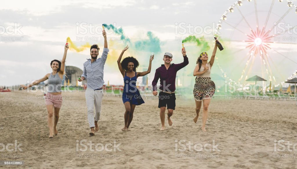Young friends running with smoke bombs and champagne bottle at beach festival - Happy people having fun in summer vacation - Friendship, youth and party concept - Main focus on left guys stock photo
