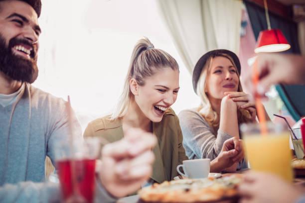 unga vänner dela pizza i en inomhus café - lunchrast bildbanksfoton och bilder