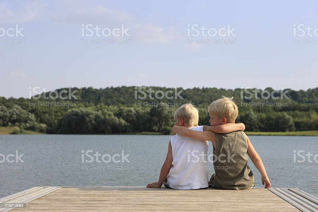 Young Friends Sitting At Jetty stock photo
