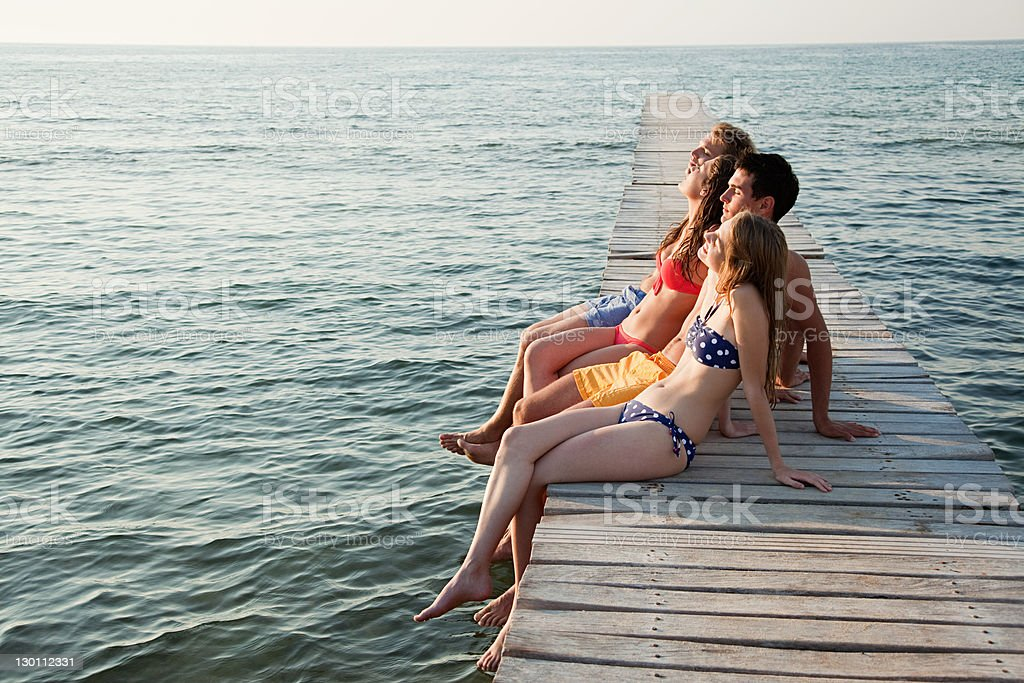 Young friends sitting on jetty stock photo
