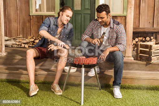 istock Young friends sitting on porch with beer bottles and and grilling meat 693640984
