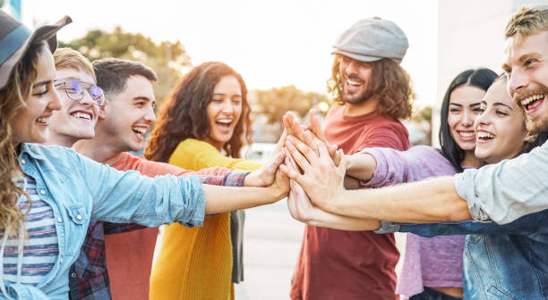 young friends stacking hands outdoor - happy millennial people having fun joining and celebrating together - friendship, empowering, teamwork, partnership and youth lifestyle concept - party social event stock pictures, royalty-free photos & images
