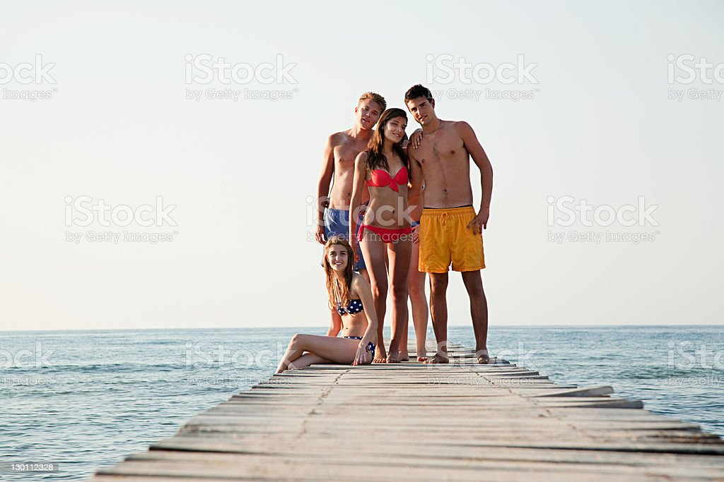 Young friends standing on jetty stock photo