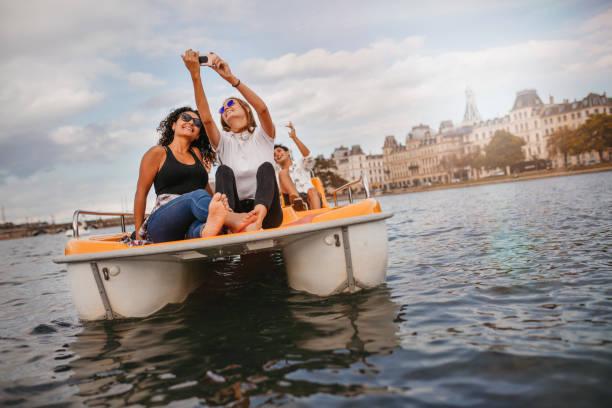 Young friends taking selfie on pedal boat - foto de stock