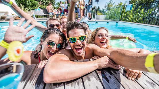 Group of young friends taking selfie at pool side during pool party.