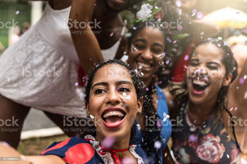 Young friends taking selfies and having fun at the carnival street stock photo
