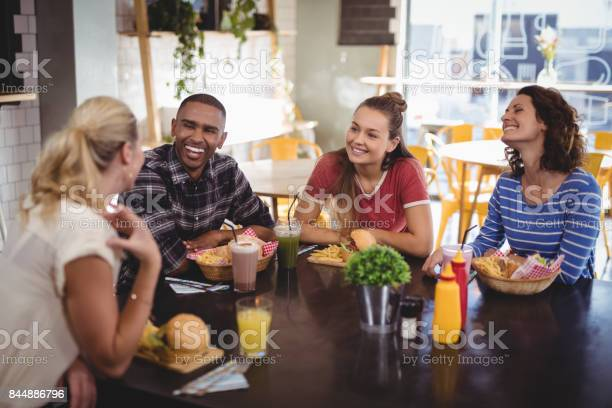 Young friends talking while sitting at table with food and drink picture id844886796?b=1&k=6&m=844886796&s=612x612&h=m0daamxphswukrpaqd05n8vxyo9ccyicdneljqiwqfy=