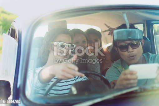 972962180istockphoto Young friends using GPS navigation on road trip 641996290