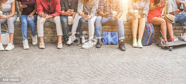 istock Young friends using smartphones and drinking coffee outdoor - Group of people having fun with technology trends - Youth, new generation addiction and friendship concept - Main focus on center guys 848195640