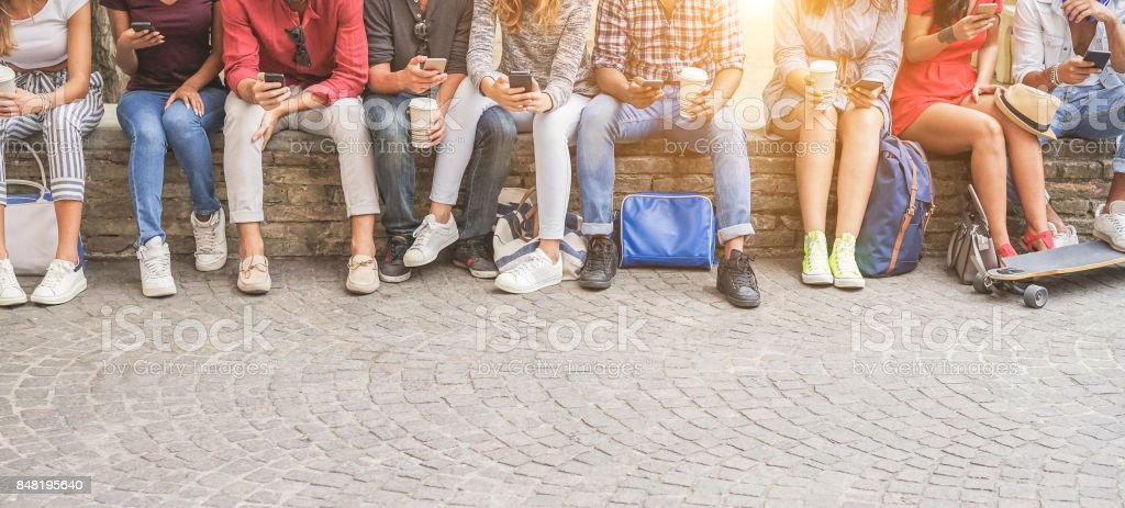 Young friends using smartphones and drinking coffee outdoor - Group of people having fun with technology trends - Youth, new generation addiction and friendship concept - Main focus on center guys stock photo