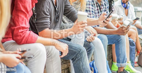 istock Young friends using smartphones and drinking coffee outdoor - Group of happy people having fun with technology trends - Youth and friendship concept - Main focus on grey t-shirt man cell hand 879357840
