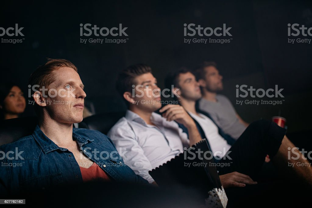 Young friends watching movie in cinema hall stock photo