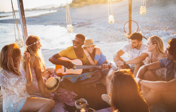 Young friends with guitar having fun at summer beach party stock photo