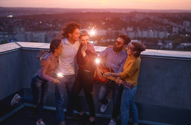Young friends with sparklers enjoying party on rooftop stock photo