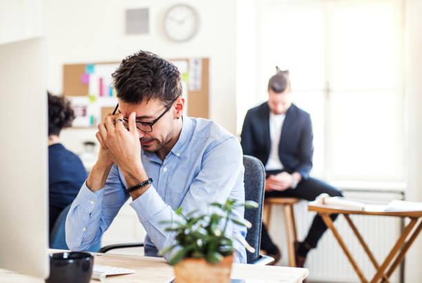 Junge frustriert Unternehmer mit Smartphone arbeiten in einem modernen Büro. – Foto