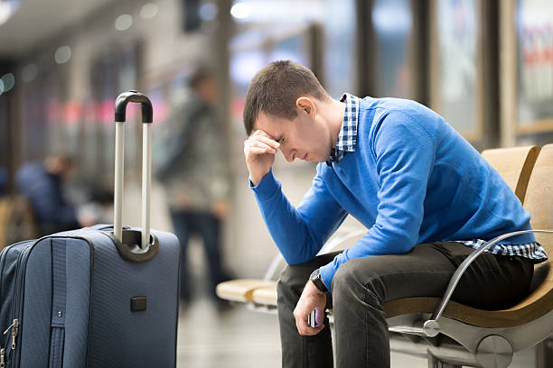 Young frustrated man at airport Portrait of young handsome guy wearing casual style clothes waiting for transport. Tired traveler man travelling with suitcase sitting with frustrated facial expression on a chair in modern station jet lag stock pictures, royalty-free photos & images