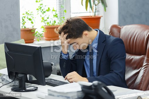 istock Young frustrated with problems young business man working on computer in office. 1086528482