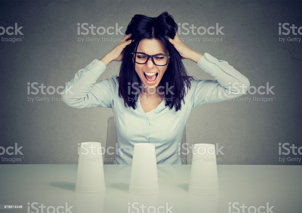 Young frustrated woman playing a conjuring trick unable to make a choice stock photo
