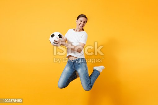 istock Young fun expressive European woman football fan jumping in air, cheer up support team, holding soccer ball isolated on yellow background. Sport, play football, cheer, fans people lifestyle concept. 1005378450