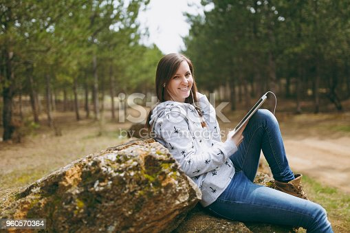 862602714istockphoto Young fun smiling beautiful woman in casual clothes with earphones sitting on stone using tablet pc computer in city park or forest on green blurred background. Student lifestyle, leisure concept. 960570364
