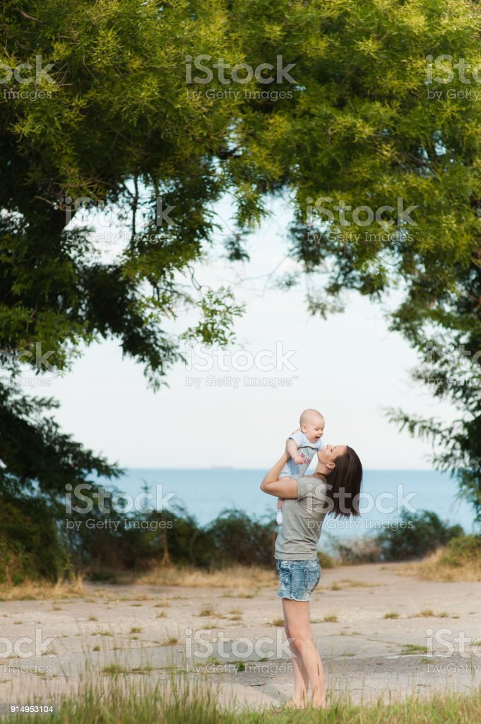 Young fun smiling woman standing at sea background hugging little cute child baby boy on nature, green trees. Mother, little kid son. Parenthood, family day 15 of may, love, parents, children concept. stock photo