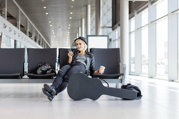 Young funky blond woman waiting for flight in airport lounge stock photo