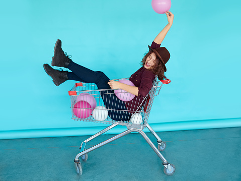 Young funky woman sitting in shopping cart over blue wall