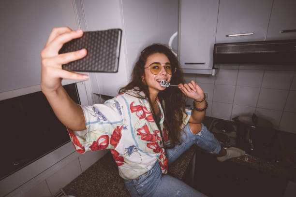 young funky woman with lollipop taking selfies at home - pics for cool girl stock pictures, royalty-free photos & images