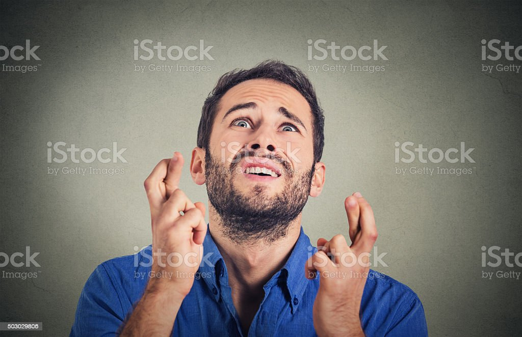 young funny business man crossing fingers wishing stock photo