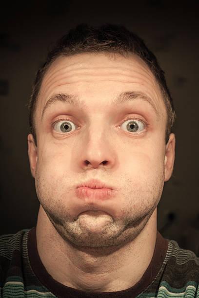 Jeune homme Caucasien drôle inflates joues.  portrait de gros plan - Photo