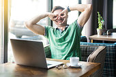istock Young funny crazy businessman in green t-shirt sitting and looking with binoculars gesture. business and freelancing concept. 1182844074