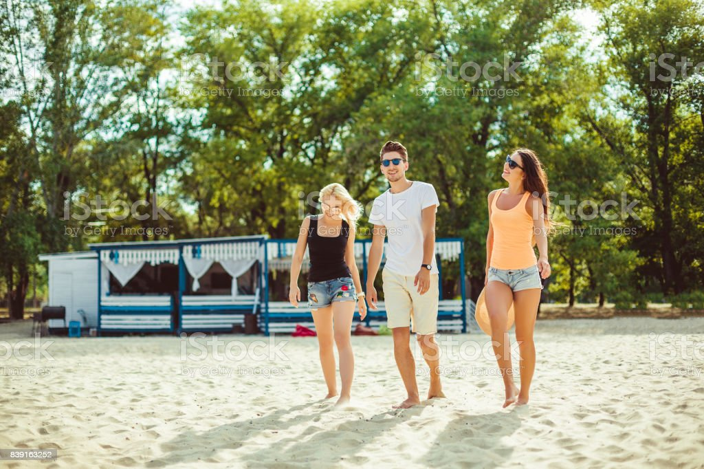 Young funny guys in sunglasses on the beach. Friends together stock photo