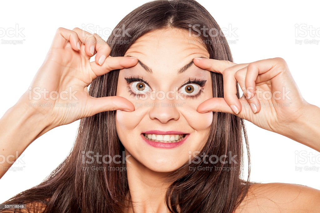 Young funny woman opening her eyes wide with fingers stock photo