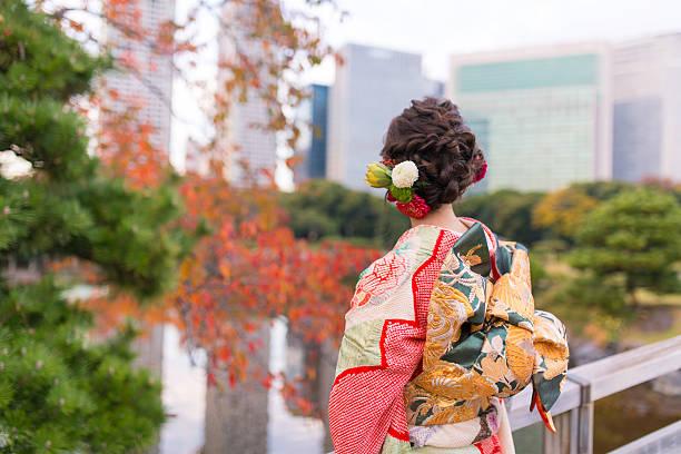 young furisode girl in autumn garden - kimono ストックフォトと画像