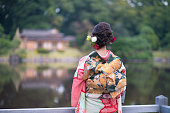 Young Furisode girl in Japanese garden