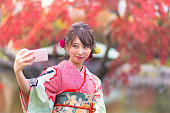 Young Furisode girl taking selfie picture in autumn foliage