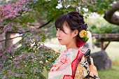 Young Furisode woman in Japanese garden