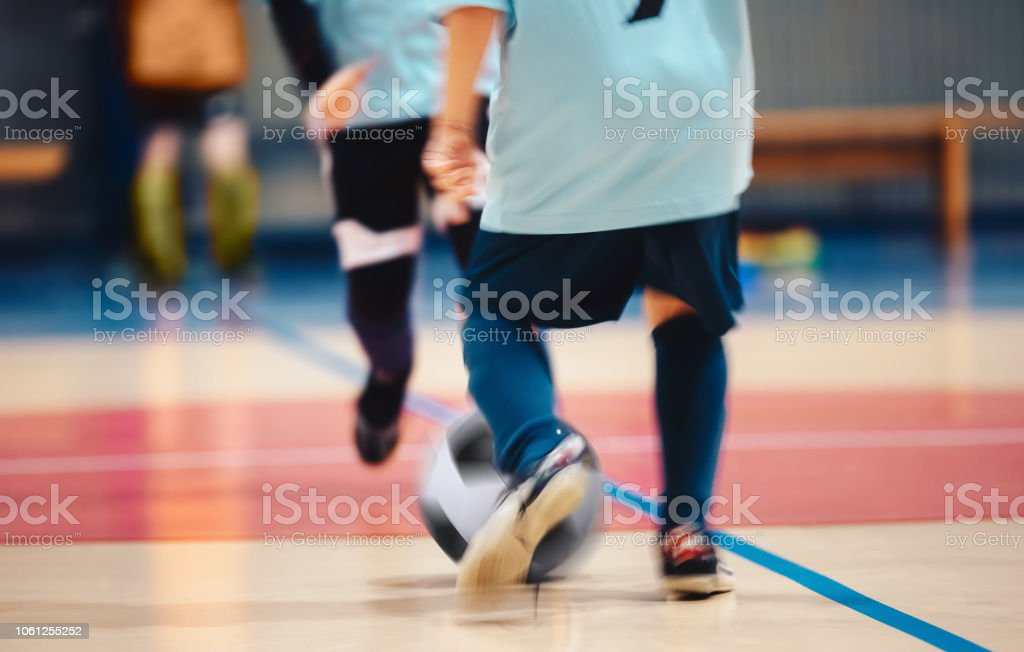 Young futsal players and soccer ball with motion blur. Indoor futsal...