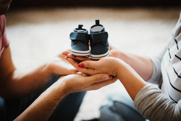 Young future parents holding baby booties shoes in their hands stock photo