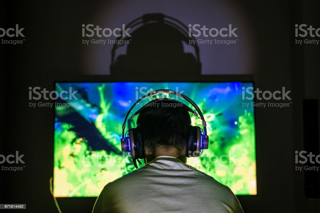 Young gamer playing video game wearing headphone. stock photo